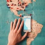 Image of an Iphone on a travel map, taking a picture of South America.