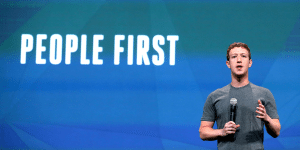 Mark Zuckerberg in front of screen that says people first.