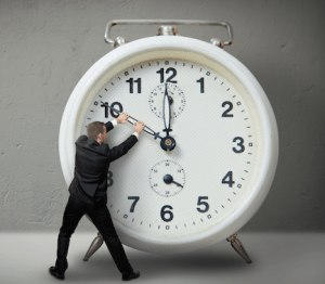This is an image of a man trying to stop the time on a large clock. He is demonstrating the necessity of time-saving apps.