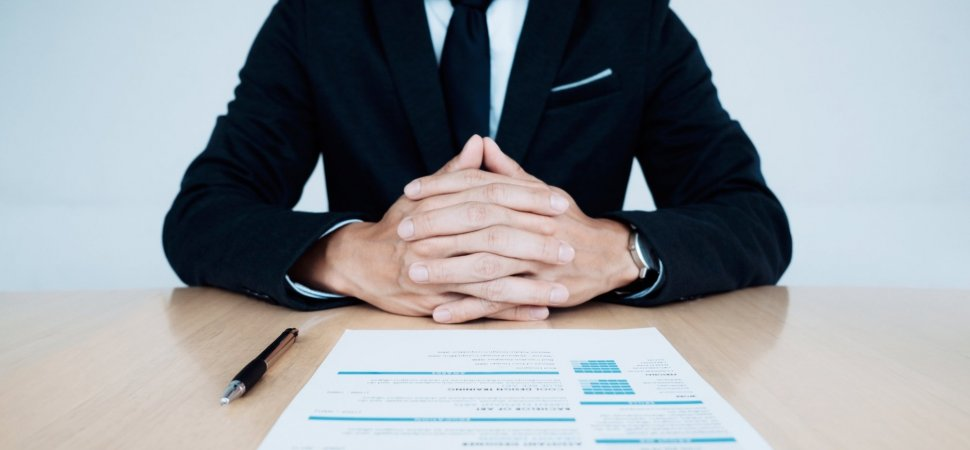 interview questions you need to know before your next interview... man sitting at a desk with his resumé in front of him